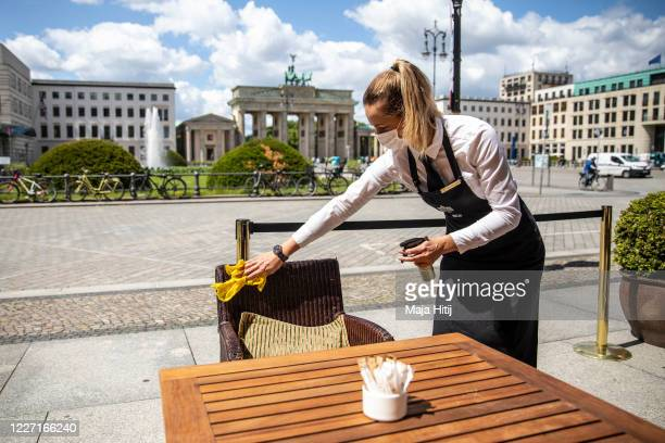 Waitress with a mouth and nose protector disinfects the table in a restaurant at the Hotel Adlon Kempinski next to the Brandenburg Gate on May 26,...