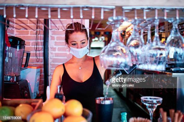 waitress with face mask preparing a cocktail at the restaurant - coronavirus and small business concept - essential services stock pictures, royalty-free photos & images
