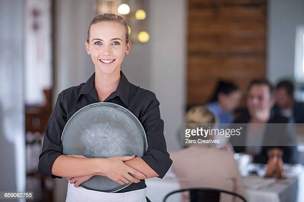 Waitress with serving tray in busy restaurant