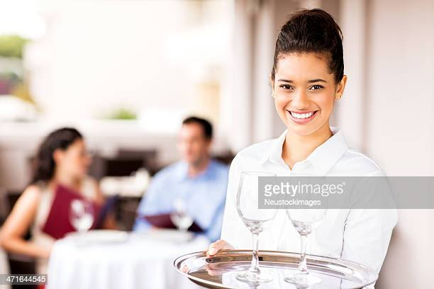 Waitress With Tray Of Wineglasses While Couple Sitting In Background