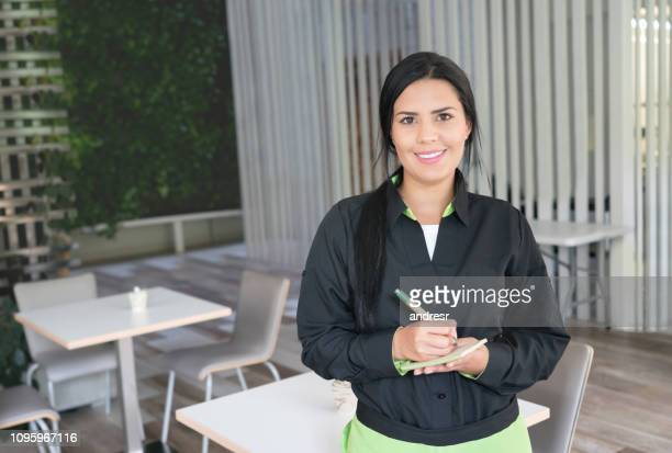 Waitress working at a restaurant holding a notepad