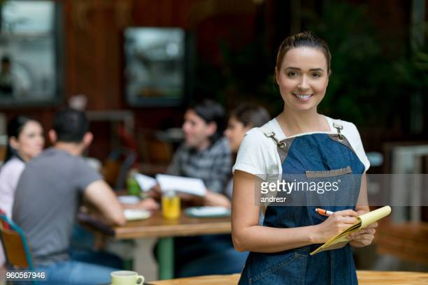 waitress working at a restaurant holding a notepad - food service occupation stock pictures, royalty-free photos & images