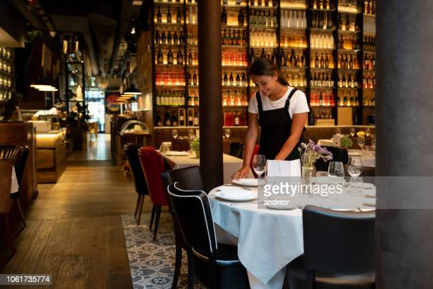 waitress working at a restaurant setting up a table - wait staff stock pictures, royalty-free photos & images