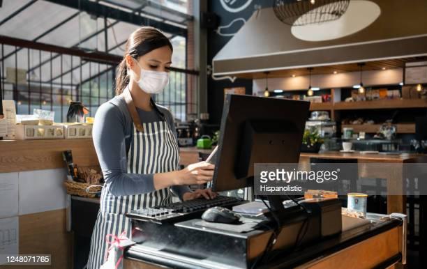 kellnerin, die in einem restaurant arbeitet und eine gesichtsmaske trägt und die bestellung im computer aufgibt - opening event stock-fotos und bilder