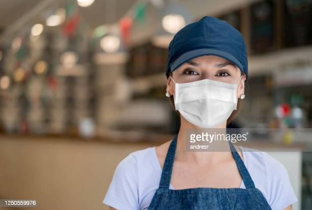 waitress working at a restaurant wearing a facemask to avoid the spread of coronavirus - biosecurity stock pictures, royalty-free photos & images