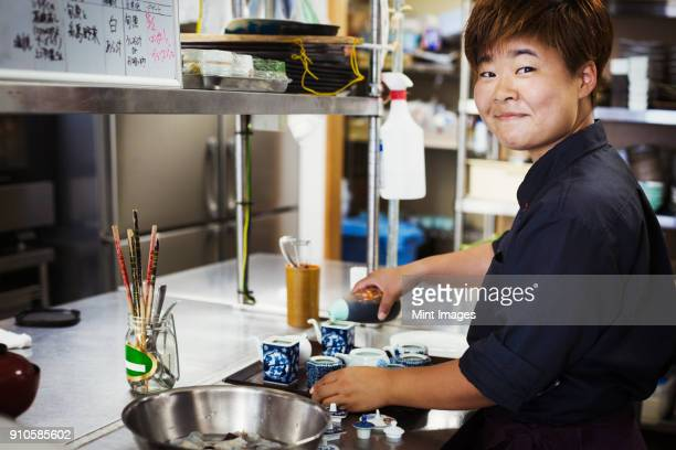Waitress working in the kitchen of a Japanese sushi restaurant, smiling at camera.