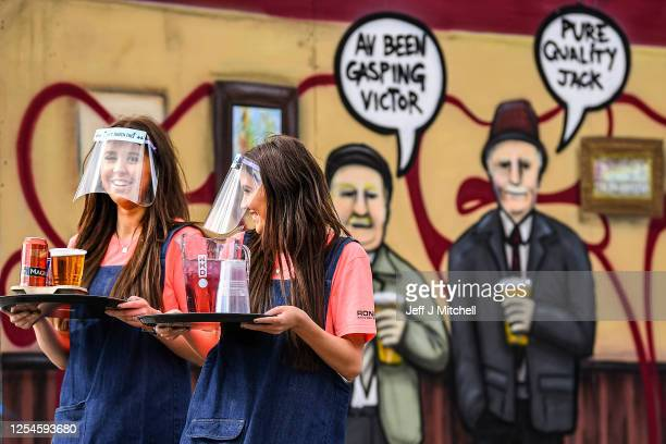 Waitresses Alex and Robyn Magowan serve members of the public as they enjoy their first drink in a beer garden at SWG3 multi – disciplinary arts...