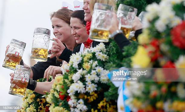 Waitresses of the Spaten brewery wave with beer mugs during the opening parade during day 1 of the Oktoberfest beer festival on September 22 2012 in...
