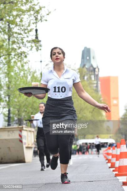 Waitresses run along the Kurfuerstendamm street during the 7th Championships of the Hotel Industry and Gastrnomy in Berlin, Germany, 7 May 2017....