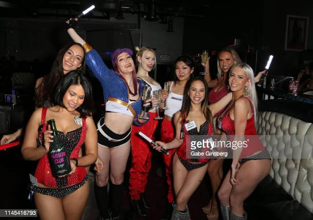 Waitstaff join cosplay models Holly Wolf Dangrrr Doll Gaius Cosplay and Eden Victoria in a champagne toast during Larry Flynt's Hustler Club The...
