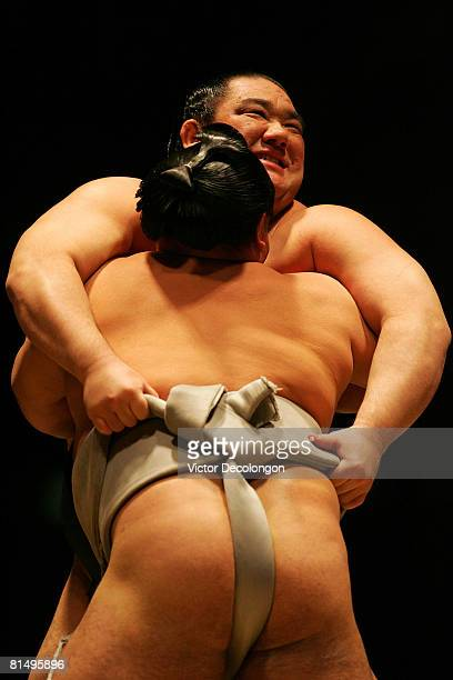 Wakanosato grabs the belt of Kakizoe en route to winning the match with a backward pivot throw or 'ucchari' during the 2008 Grand Sumo Tournament at...