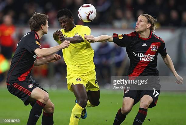 Wakaso Mubarak of Villarreal is challenged by Daniel Schwaab and Domagoj Vida of Leverkusen during the UEFA Europa League round of 16 first leg match...