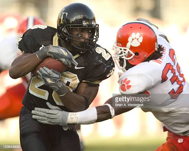 Wake Forest RB Chris Barclay tries to avoid the grasp of Clemson LB Nick Watkins during second half action at Groves Stadium in Winston-Sale, NC,...