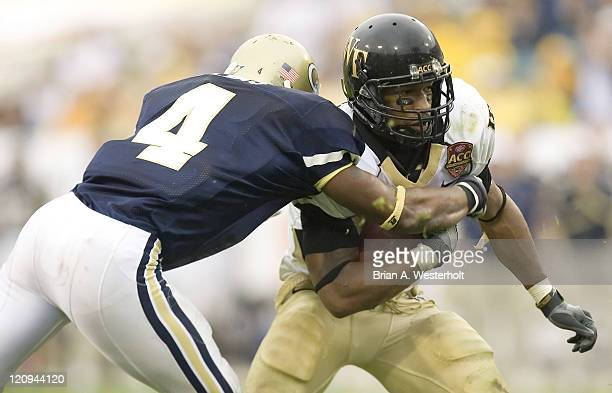 Wake Forest running back Kenneth Moore is wrapped up by Georgia Tech safety Jamal Lewis during the ACC Championship at Alltel Stadium in Jacksonville...
