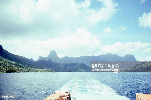 Wake of a pleasure boat, a commercial ship in the distance, traveling through a harbor with tropical mountains visible in the background, with blue...