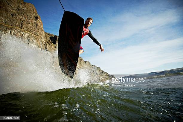 Wakeboarder jumping over wake view from below