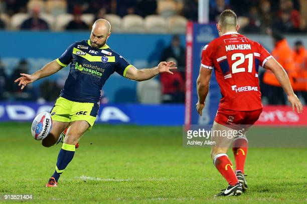 Wakefield Trinity's Liam Finn kicks the all down the ground as Hull KR's Robbie Mulhern looks on during the BetFred Super League match between Hull...