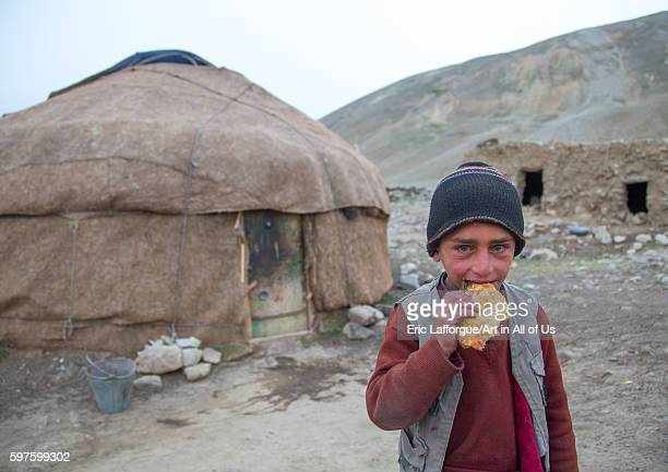 Wakhi nomad boy eating bread in front of his yurt big pamir wakhan Afghanistan on August 12 2016 in Wakhan Afghanistan
