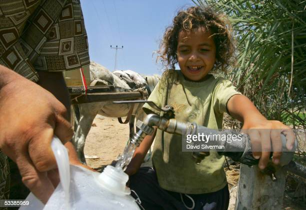 Walah Beni Ammer a fiveyearold Palestinian girl watches as her father Abdel Kareem Beni Ammer fills plastic bottles with water August 14 2005 in the...