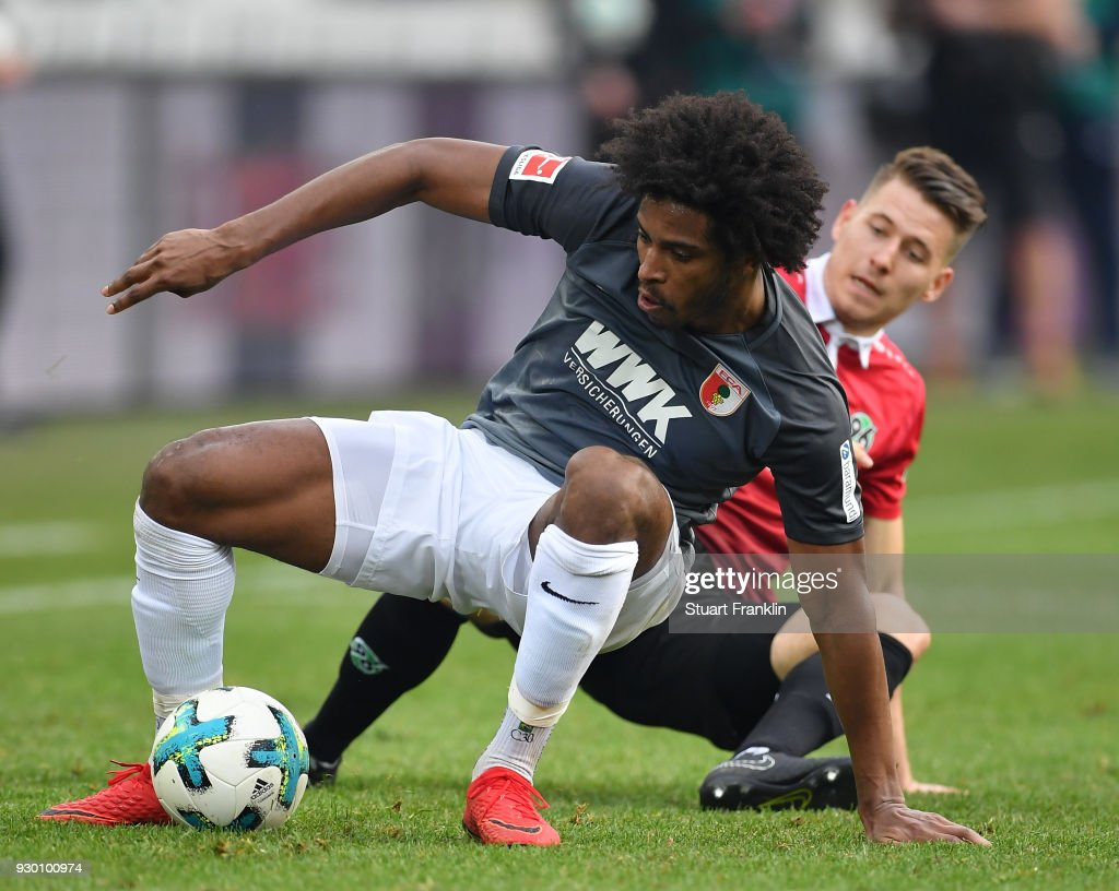 Waldemar Anton of Hannover is challenged by Caiuby of Augsburg during the Bundesliga match between Hannover 96 and FC Augsburg at HDI-Arena on March 10, 2018 in Hanover, Germany.