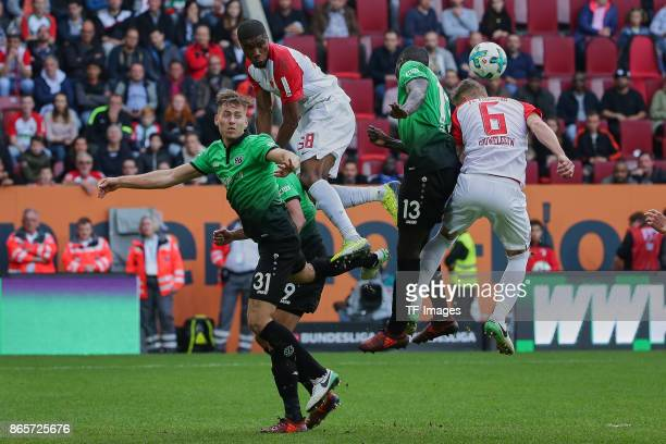 Waldemar Anton of Hannover Kevin Danso of Augsburg Ihlas Bebou of Hannover and Jeffrey Gouweleeuw of Augsburg battle for the ball during the...