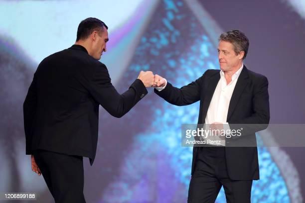 Waldimir Klitschko and host Hugh Grant joke on stage during the 2020 Laureus World Sports Awards at Verti Music Hall on February 17 2020 in Berlin...