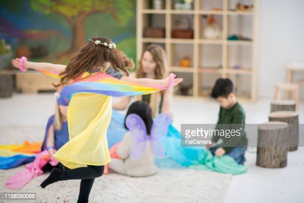 waldorf elementary kids trying on costumes and dancing - montessori education stock pictures, royalty-free photos & images