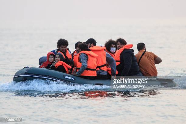Waleed a Kuwaiti migrant, sits in a dinghy with other migrants as they illegally cross the English Channel from France to Britain on September 11,...