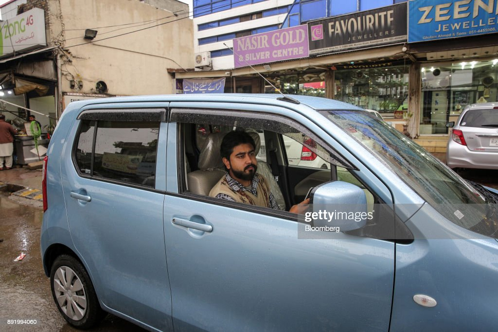 Waleed Ali a Careem Inc driver known as a captain uses his smartphone while waiting for a customer in his car on Murree Road in Rawalpindi Pakistan...