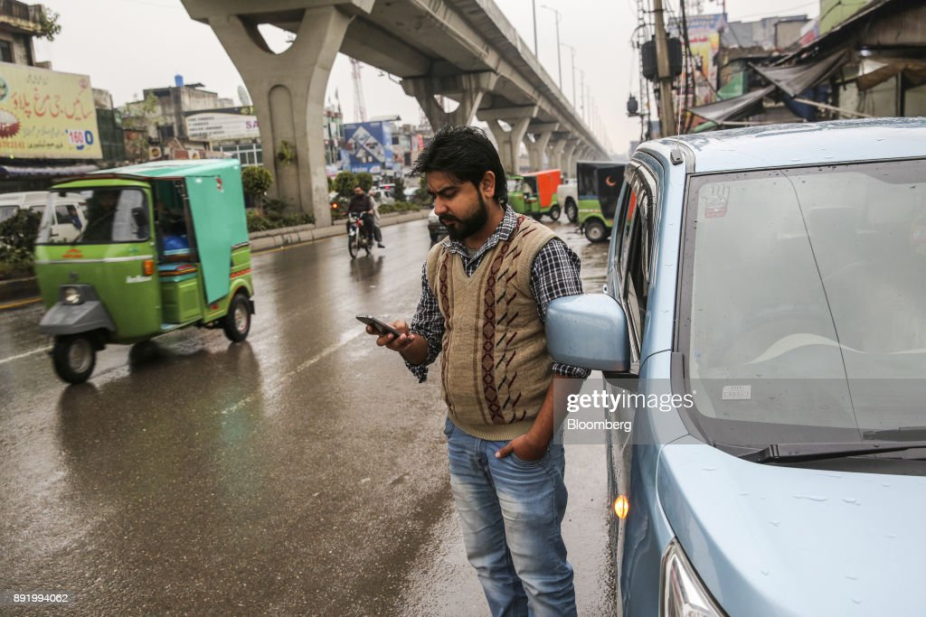 Waleed Ali a Careem Inc driver known as a captain uses his smartphone while waiting for a customer next to his parked car on Murree Road in...