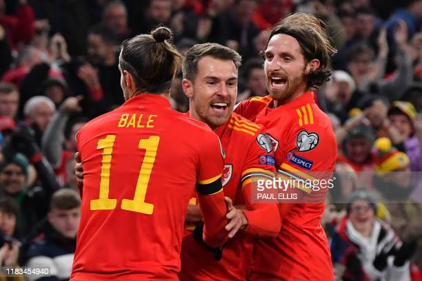 Wales' Aaron Ramsey celebrates with Wales' forward Gareth Bale and Wales' midfielder Joe Allen after scoring his team's first goal during the Group E...