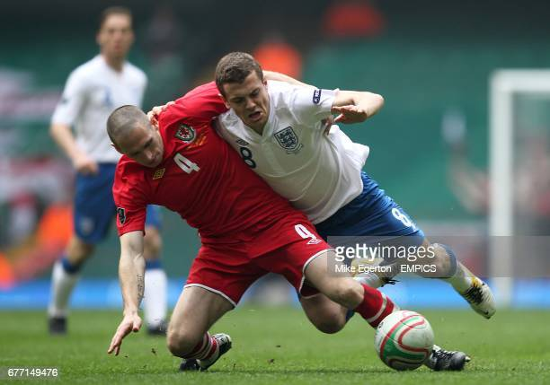 Wales' Andrew Crofts and England's Jack Wilshere fall to the floor after battling for the ball