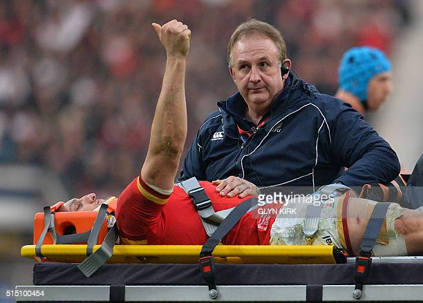 Wales' captain and flanker Sam Warburton gestures as he is taken from the field on a stretcher after picking up an injury during the Six Nations...