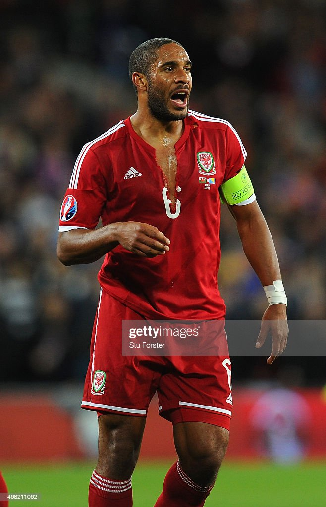 Wales captain Ashey Williams with a ripped shirt reacts during the EURO 2016 Qualifier match between Wales and Bosnia and Herzegovina at Cardiff City Stadium on October 10, 2014 in Cardiff, Wales.