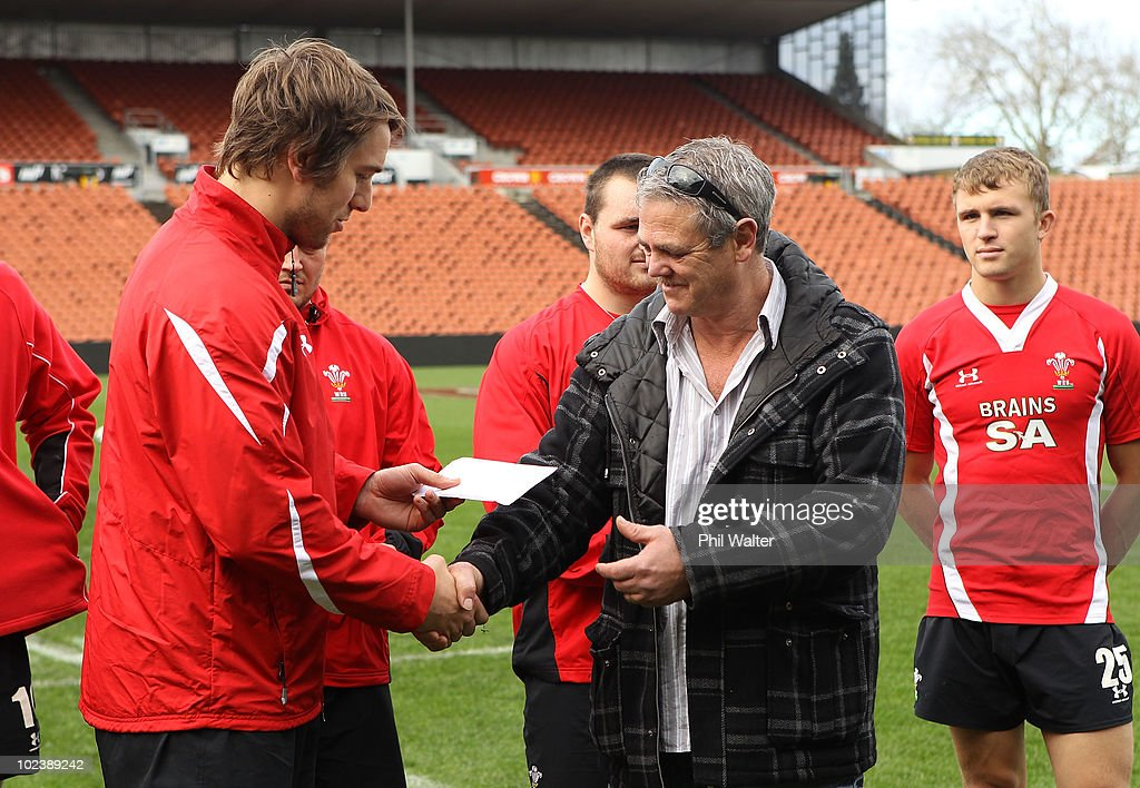 Wales captain Ryan Jones (L) presents money to a local charity organisation following the Wales Captain's Run at Waikato Stadium on June 25, 2010 in Hamilton, New Zealand.