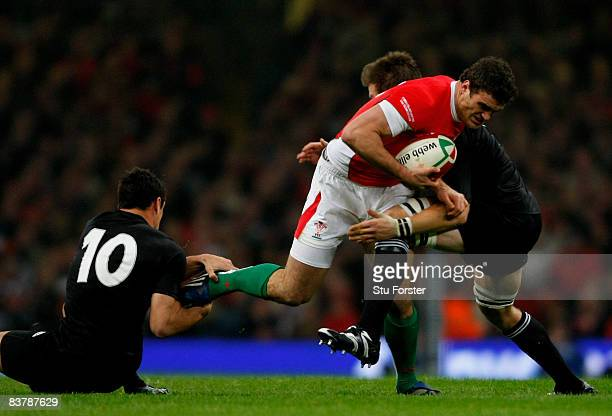 Wales centre Jamie Roberts is tackled by Dan Carter and Richie McCaw during the Invesco Perpetual Series match between Wales and New Zealand All...