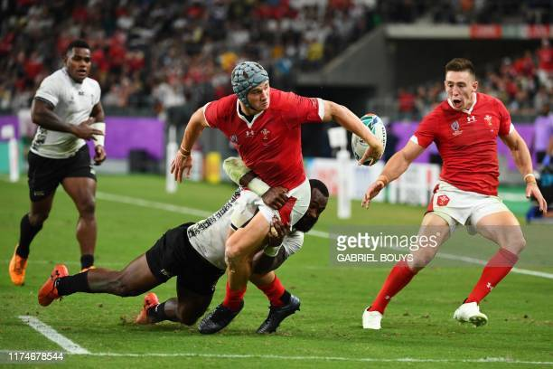 Wales' centre Jonathan Davies passes the ball to Wales' wing Joshua Adams after being tackled by Fiji's wing Josua Tuisova during the Japan 2019...