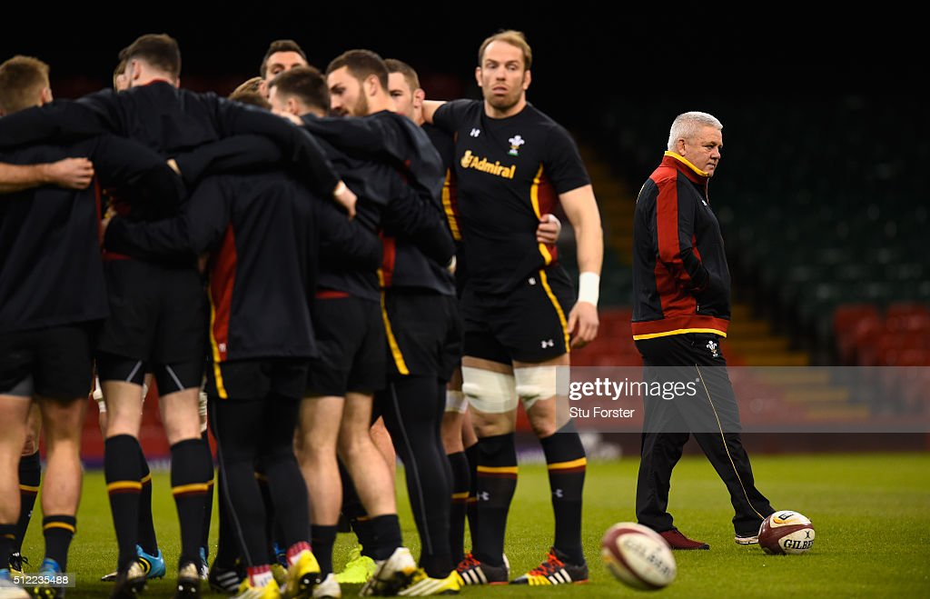 Wales coach Warren Gatland (r) looks on as his team engage in a huddle during the Wales captain's run ahead of their RBS Six Nations match against France at Principality Stadium on February 25, 2016 in Cardiff, Wales.