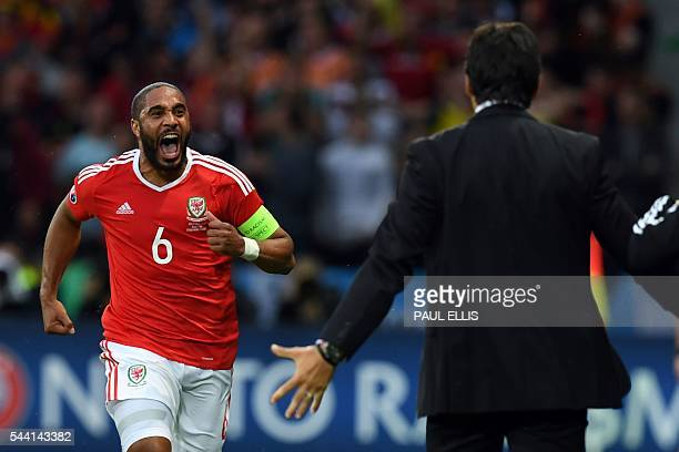 Wales' defender Ashley Williams celebrates after scoring a goal with Wales' coach Chris Coleman during the Euro 2016 quarterfinal football match...
