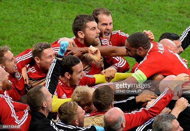 Wales' defender Ashley Williams celebrates with teammates after scoring a goal during the Euro 2016 quarterfinal football match between Wales and...