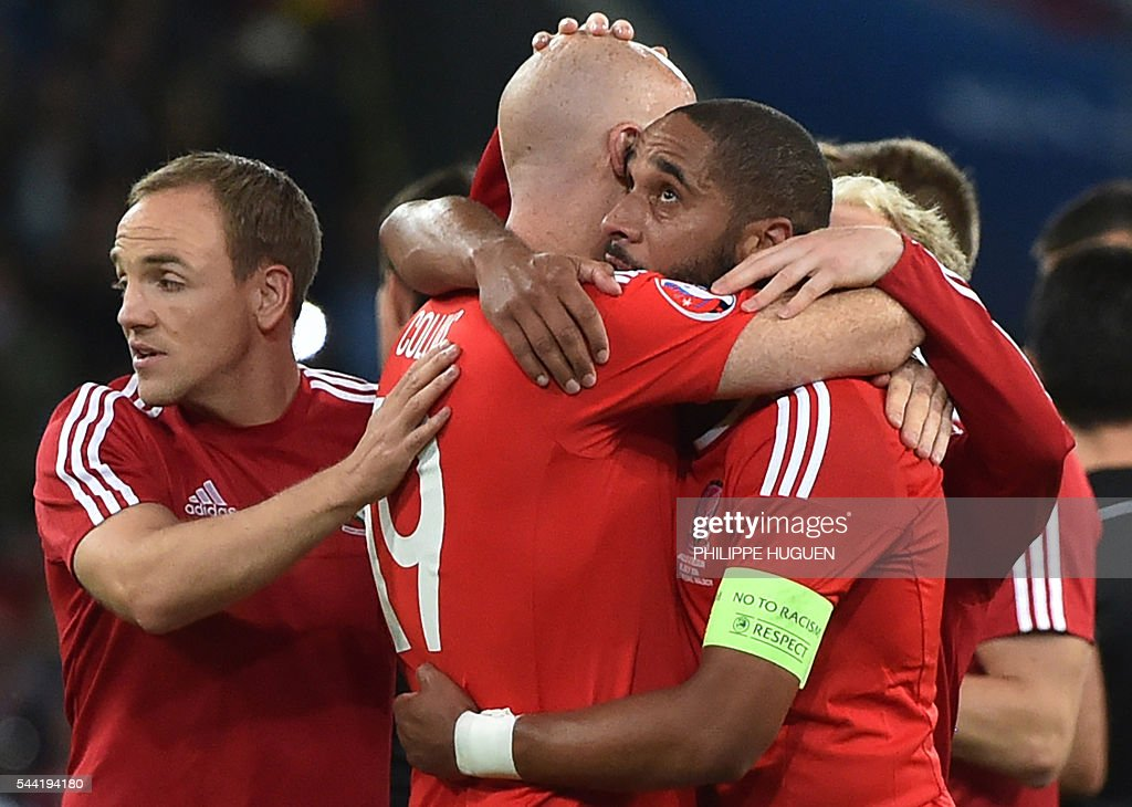 Wales' defender Ashley Williams (R) celebrates with Wales' defender James Collins at the end of the Euro 2016 quarter-final football match between Wales and Belgium at the Pierre-Mauroy stadium in Villeneuve-d'Ascq near Lille, on July 1, 2016. / AFP / PHILIPPE