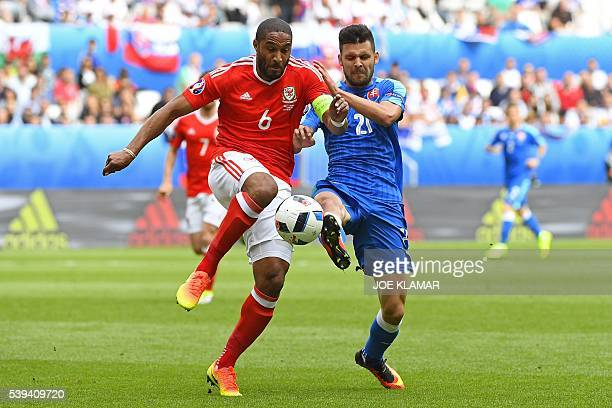 Wales' defender Ashley Williams vies for the ball with Slovakia's forward Michal Duris during the Euro 2016 group B football match between Wales and...