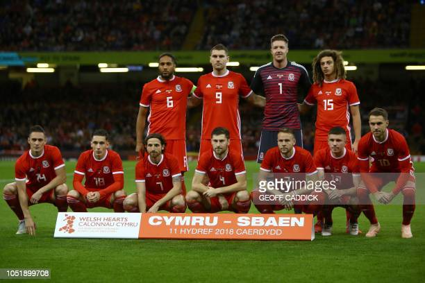 Wales' defender Ashley Williams Wales' striker Sam Vokes Wales' goalkeeper Wayne Hennessey and Wales' defender Ethan Ampadu stand with teammates...