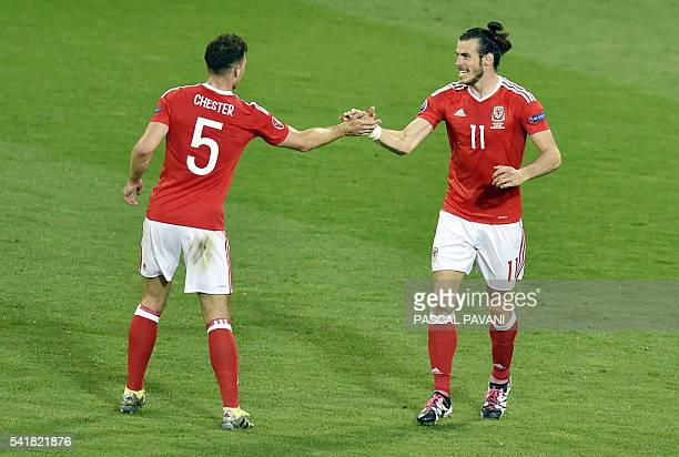 TOPSHOT Wales' defender James Chester congratulates Wales' forward Gareth Bale on scoring the team's third goal during the Euro 2016 group B football...