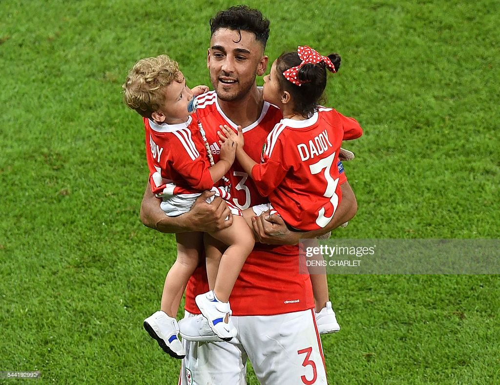 Wales' defender Neil Taylor celebrates with his children Madison and Marley at the end of the Euro 2016 quarter-final football match between Wales and Belgium at the Pierre-Mauroy stadium in Villeneuve-d'Ascq near Lille, on July 1, 2016. / AFP / DENIS
