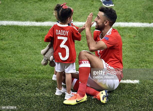 Wales' defender Neil Taylor celebrates with his children the team's 30 win in the Euro 2016 group B football match between Russia and Wales at the...