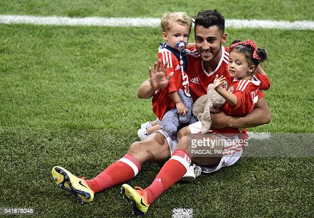Wales' defender Neil Taylor holds his children as he celebrates the team's 30 win in the Euro 2016 group B football match between Russia and Wales at...