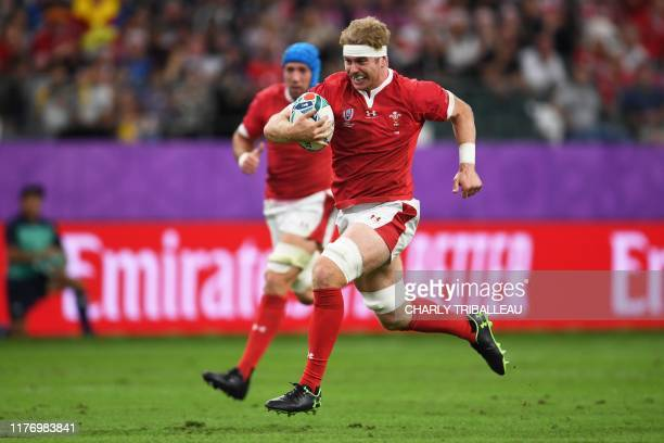 Wales' flanker Aaron Wainwright runs to score a try during the Japan 2019 Rugby World Cup quarterfinal match between Wales and France at the Oita...