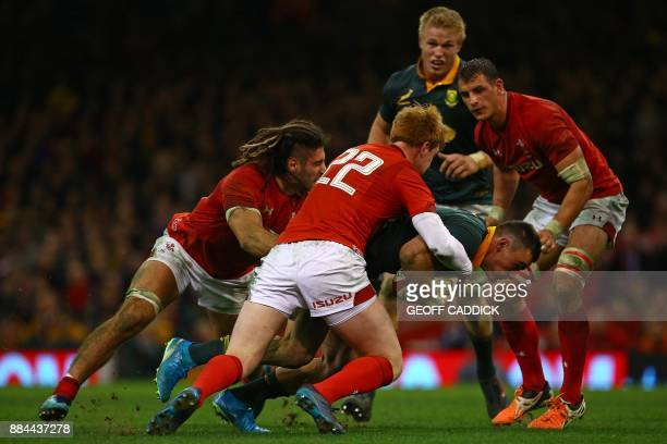 Wales' flanker Josh Navidi and Wales' Rhys Patchell tackle South Africa's centre Jesse Kriel during the international rugby union test match between...