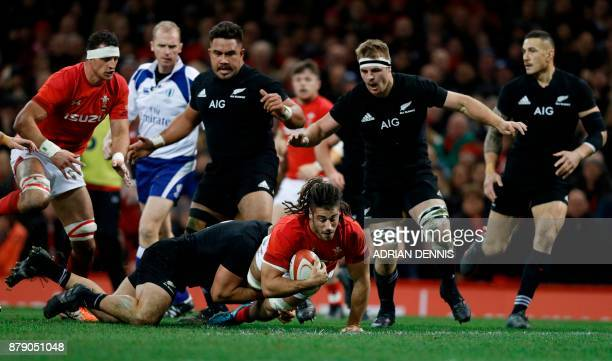 Wales' flanker Josh Navidi is tackled by New Zealand's hooker Codie Taylor as Navidi tries to break through during the autumn international rugby...